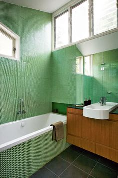 emerald green penny tiles, white grout, floating wood cabinet, charcoal tile floors, white fixtures, clerestory bathroom window