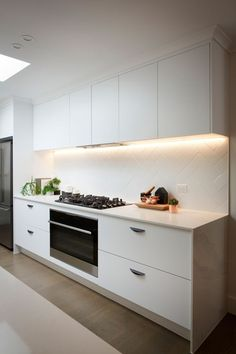 Kitchen all-white quartz countertop and tiled backsplash