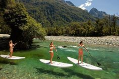 Paddle boarding on the Hollyford track in New Zealand #newzealandtrails #activeadventures #hollyfordtrack #besthikingtrails #bestwalkingtrails