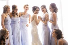 Candid photo of bride and bridesmaids laughing while bride is getting dresses bridesmaids in light blue one shoulder dress - Photos by Jenny & Eddie