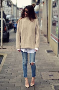 layered street style look with neutral cozy knit sweater, classic white button down and boyfriend jeans.