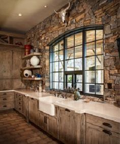 Rustic kitchen with plank cabinets and brick wall with arched window
