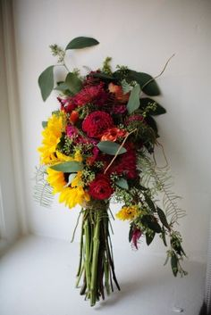 Wedding bridal bouquet: sunflowers, ranunculas, greens, burlap twine tie and unclipped loose stems, carried over one arm. #9172011