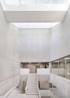 A central atrium with a concrete staircase opens the space up and connects the different levels. Concrete Staircase, Expanded Metal, Sport Hall, Exposed Concrete, School Sports, Roof Design, Atrium, Alps, Zig Zag