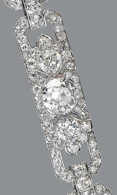 An art deco diamond bracelet, by Hennell, circa 1930 The three old brilliant-cut diamond articulated panels, each set to the centre with a principal diamond between palmette motifs, within an openwork geometric frame, connected by rectangular buckle-shaped links, diamonds approximately 18.20 carats total, signed Hennell, length 18.4cm.