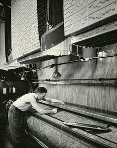 A weaver adjusts a #jacquard loom/Corbis. If you look at the top of the picture you'll see the holes that are punched in cards. Those are the patterns.