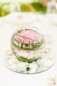 Table Centerpeice of Pink Blush Peony and Grass Shards in Glass Fish Bowl on Round Mirror with White Petals and White Tea Candles.