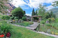 Blick zur idyllischen Gartenlaube hinter dem Teich