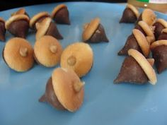 cute and easy to put on a fall cake--Decorative and tasty acorns made with hershey kisses, mini Nilla wafers and itty bitty peanut butter morsels (from a sprinkle mix)--site has additional fall party food ideas