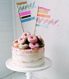 White Round Birthday Cake with Donuts stacked on top