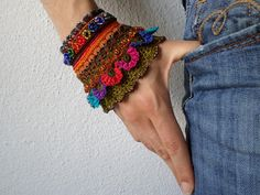 Starting with a crocheted orange base, this bracelet has various beaded flowery details in indigo blue, red, orange, green, pink, grey,