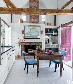 In the kitchen, a vintage light from Ann-Morris is suspended above a French table that used to belong to Bunny Mellon; the tile above the Viking range is by Ann Sacks, and P. Allen Smith painted the large watercolor.