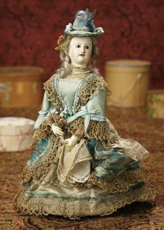 """French Paper Mache Mechanical """"Girl with Flowers"""" Attributed to Theroude~~~~11""""wearing original elaborate aqua silk dress with lace and ribbon trim and matching bonnet, and carries a small bouquet of flowers. When wound, the wheeled hidden platform glides forward and in circles, while the girl turns her head briskly from side to side and moves her arms up and down. Comments: attributed to Theroude, Paris, circa 1850."""