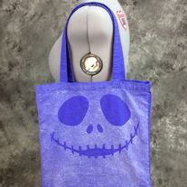 Bleach Dyed blueberry bag with a happy skull design on it. Design is dyed on both sides. Perfect for Halloween, conventions, trips to the comic shop, as a reusable shopping bag or as a purse.  Blueberry (Blueish purple) 100% cotton canvas promo bag (thinner than reg. canvas bags from the craft ...