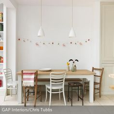 Der Mix aus verschiedenen Vintage-Stühlen verleiht dem hellen Essbereich seinen ganz speziellen Charme. Im Mittelpunkt steht der große Holztisch mit passender …
