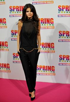 For the Rome photocall for Spring Breakers, Selena Gomez chose a black Thomas Wylde jumpsuit with gold chai...