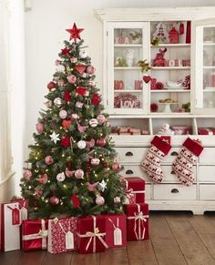 Beautiful Christmas Decorations, stockings, and Christmas Gift Wrapping in a Red and White themed kitchen, all topped off with red and white tree ornaments and a red star atop the Christmas tree.