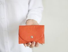 Small wallet made of buttery soft cowhide in tangerine . It has 2 card slots (each slot holds up to five cards), one bigger slot, a back zipper pocket and one big case for banknotes or coins. Wallet closes with a snap button in gold or silver. This style is although available in pale lemon or black leather.  Size : H 8.5 x W 11.5 x D 1.5 cm // H 3.4 x W 4.5 x D 0.5 ______________________________________________________________ Designed and hand made with love and care in Berlin All ...