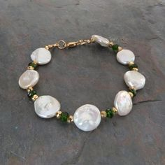 This handmade pearl and gemstone bracelet stands out with high quality genuine 10mm white coin pearls mixed with AAA faceted chrome diopside gemstones with a gorgeous beautiful deep emerald green color. Faceted gold pyrite gemstone nuggets accent the stones. The pearls are genuine