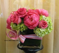 Hot pink Peony accented with Ecuadorian Roses and Hydrangeas arranged in a low square glass vase.