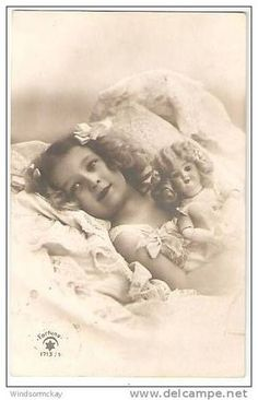 little girl tucked into bed with her dolly