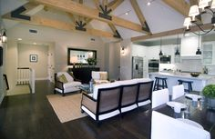 Living room in a modern farm house by Meredith Baer with truss-beamed ceiling, dark wood floor, white armchairs with wood arms and a matching sofa