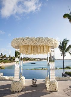 For a beachfront wedding, Jeff Leatham decorated a dramatic, mirrored chuppah with hundreds of white blooms.