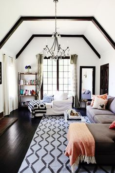 Dark hardwood floor a, white contrasting walls, exposed beams, high ceilings, chandelier.