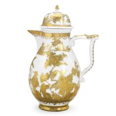 A MEISSEN HAUSMALER COFFEE POT AND COVER CIRCA 1730 the underglaze blue decoration overpainted in etched gilding, probably in the Seuter workshop in Augsburg, with chinoiserie figures amongst tall flowering shrubs and birds beneath a foliate and C-scroll border, set with wishbone handle