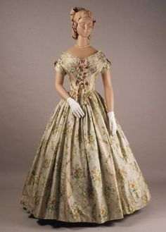 1840-1849. 18th C style, silk brocaded with ribbon stripes and garlands, and flowers in blue, red and mauve, wide neck, cap sleeves, V front, full skirt (originally separate). Belt: trimmed with repeated bows.