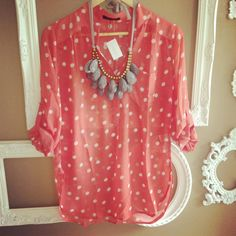 Peach polka-dot blouse and grey teardrop bib necklace.