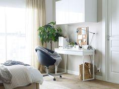 Et hvidt skrivebord, en sort kontorstol med hjul og et vægskab i et soveværelse.
