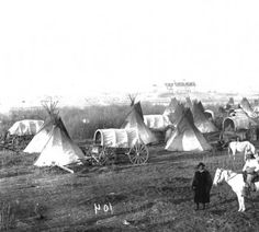 Young Man Afraid Of His Horses, a Native American (Oglala Sioux) man, poses with another man on horseback near a group of tepees on the Pine Ridge Agency, South Dakota. Covered wagons and families are in the camp. An agency building is in the distance.