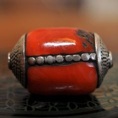 Ancient silver capped and decorated red Tibetian coral bead| vividvault