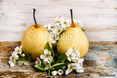 yellow pears and pear flowers on vintage wood background