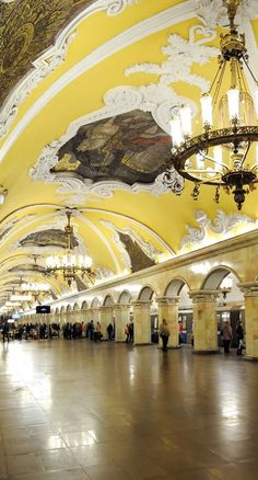 "Komsomolskaya subway station in Moscow, Russia. (Koltsevaya Line) - photo from ...;  The station opened in 1952. It has an ""imposing Baroque ceiling, with accompanying friezes, painted yellow. Supporting the ... barrel vault are 68 octagonal columns faced with white marble, and topped with baroque pilasters. The platform is lit up by chandeliers and additional concealed elements in the niches of both the central and platform halls."" There are 8 large ceiling mosaics by Pavel Korin."