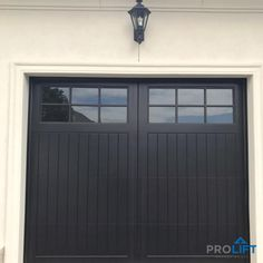 This garage door has it all! There's a perfect mix of carriage house style with lantern lighting, trending color (black) and modern overhead garage door technology. Very nice indeed. | ProLift Garage Doors on Houzz | Project and Photo Credits: ProLift Garage Doors in Haymarket, Virginia