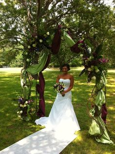 Iron arch with sahara roses, green orchids, purple larkspur, green trick, satin fabric and grapevine