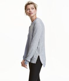 Light gray melange. CONSCIOUS. Fine-knit sweater with wool content. Zip at sides, ribbing at neckline, cuffs, and hem, and a slightly longer back section.