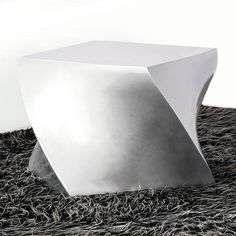 "A perfect seat for the modern minimalist home, the Twisted Cube Ottoman has a sleek surface and ""twisting"" lines that give the piece some movement."