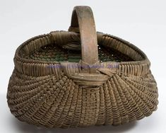 """Price Realized: 287.50 APPALACHIAN RIB-TYPE PAINTED WOVEN SPLINT EGGBASKET, white oak, very finely woven kidney form with delicate double rim, arched handle featuring unusual stepped handle supports, and fancy over-woven base rib. Old dry oxidized gold paint over the original green paint. Probably Virginia or Maryland. Late 19th/first quarter 20th century. 5 1/4"""" HOA, 3 1/2"""" H rim, 5"""" x 6"""" D rim. Provenance: From a 35-year Augusta Co., VA collection."""