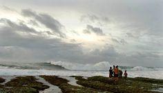 Menunggu ombak dengan Berdiri di atas terumbu karang di Pantai Sayang Heulang, Garut, Jawa Barat