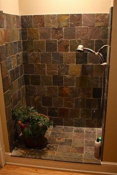 dar tiled shower cabin with flower in it