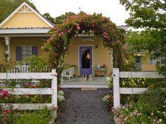 "The ""Peggy Martin"" rose adorns an arbor above a gate to the old farmhouse near Brenham. Photo: Molly Glentzer"