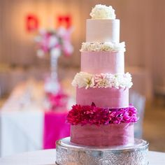 Four tier pink ombre cake decorated with dahlias between each layer.