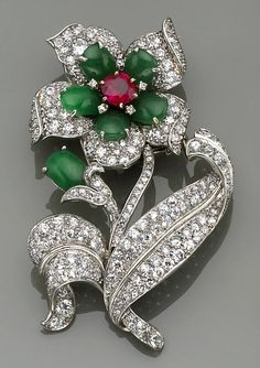 A diamond, ruby and jadeite jade convertible brooch-pendant of floral design, the removable flower centering a cushion-shaped ruby, within a surround of jadeite jade, and petals of round brilliant and single-cut diamonds, completed by a jadeite bud and flowing leafs of round brilliant and single-cut diamonds; estimated total diamond weight: 4.60 carats; mounted in platinum.