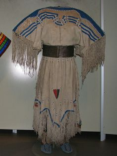 Piegan (Blackfoot) two-hide dress, ca. 1850: Canada. Hide, pony beads, blue and red wool, sinew;  Harness leather, brass tacks, hide; Blood (Blackfoot) moccasins, ca. 1880: Canada. Hide, seed beads, cloth, rawhide, canvas, sinew, thread.  The beadwork on the yoke focuses the eye on where the tail would be, and triangular trade-cloth patches represent the heads of the animals whose hides form the dress.