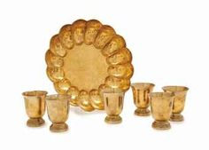 AN ENGLISH SILVER-GILT SCALLOPED CENTERBOWL, A SET OF EIGHT FRENCH GILT-PLATE BEAKERS, THE BOWL OF TIFFANY & CO. AS RETAILER, LONDON, 1968, THE BEAKERS MARK OF CHRISTOFLE, THIRD QUARTER 20TH CENTURY.