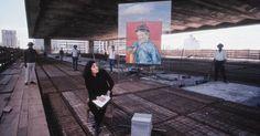"""Lina Bo Bardi posa para foto junto a obra """"O Escolar"""" de van Gogh e operarios trabalhando na construcao do MASP."""
