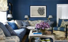 """""""The whole family watches TV on the sectional in the sitting room,"""" Sikes says of this nook upstairs. """"Dark walls make it especially cozy."""" The cushions on the Redford House armchair are covered in Peter Dunham Textiles' Ikat fabric. The Visual Comfort sconces have shades in a Lisa Fine Textiles linen."""